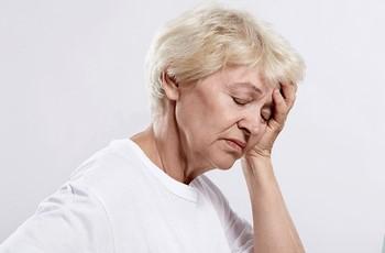 Пожилая женщина держится за голову