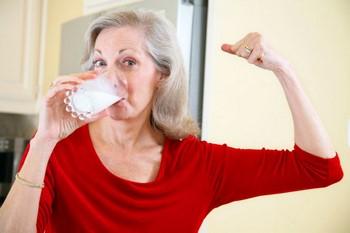 Пожилая женщина пьет молоко