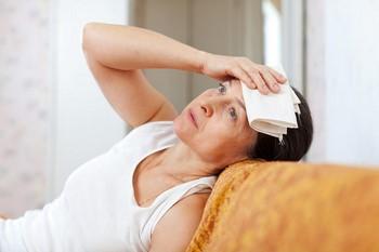 Женщина приложила полотенце к голове