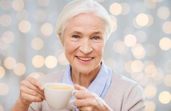 Пожилая женщина пьет чай